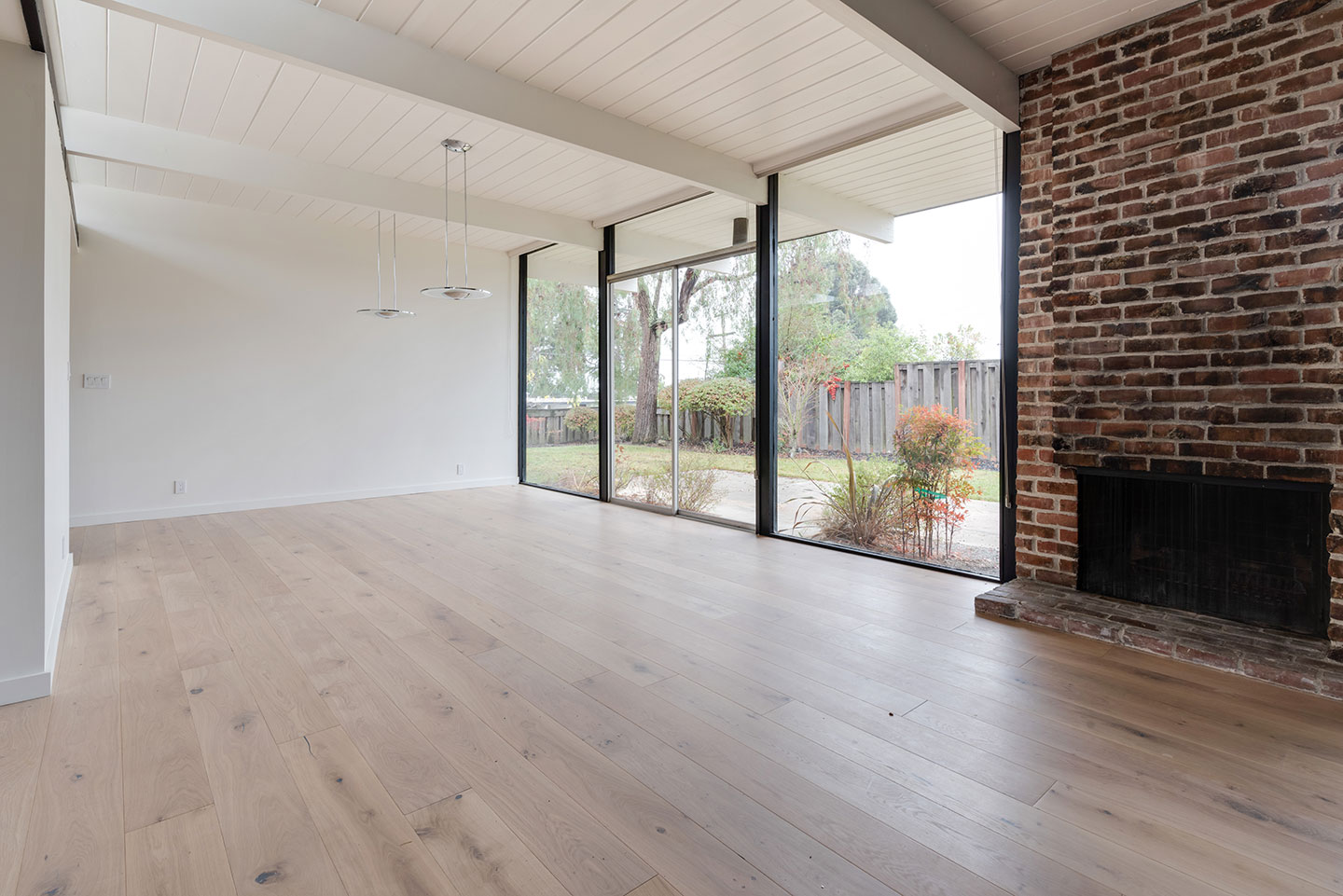 brick fireplace next to floor to ceiling windows