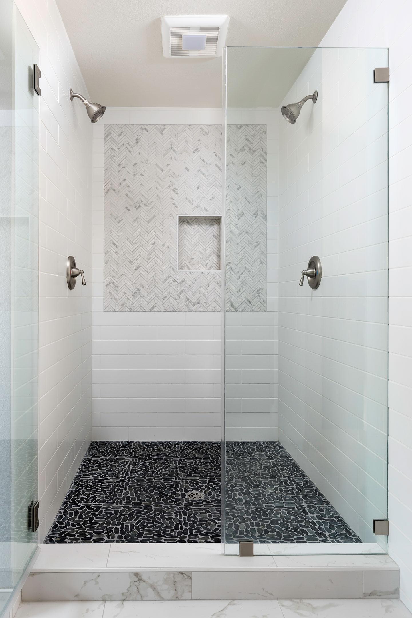 glass shower enclosure with black pebble floor