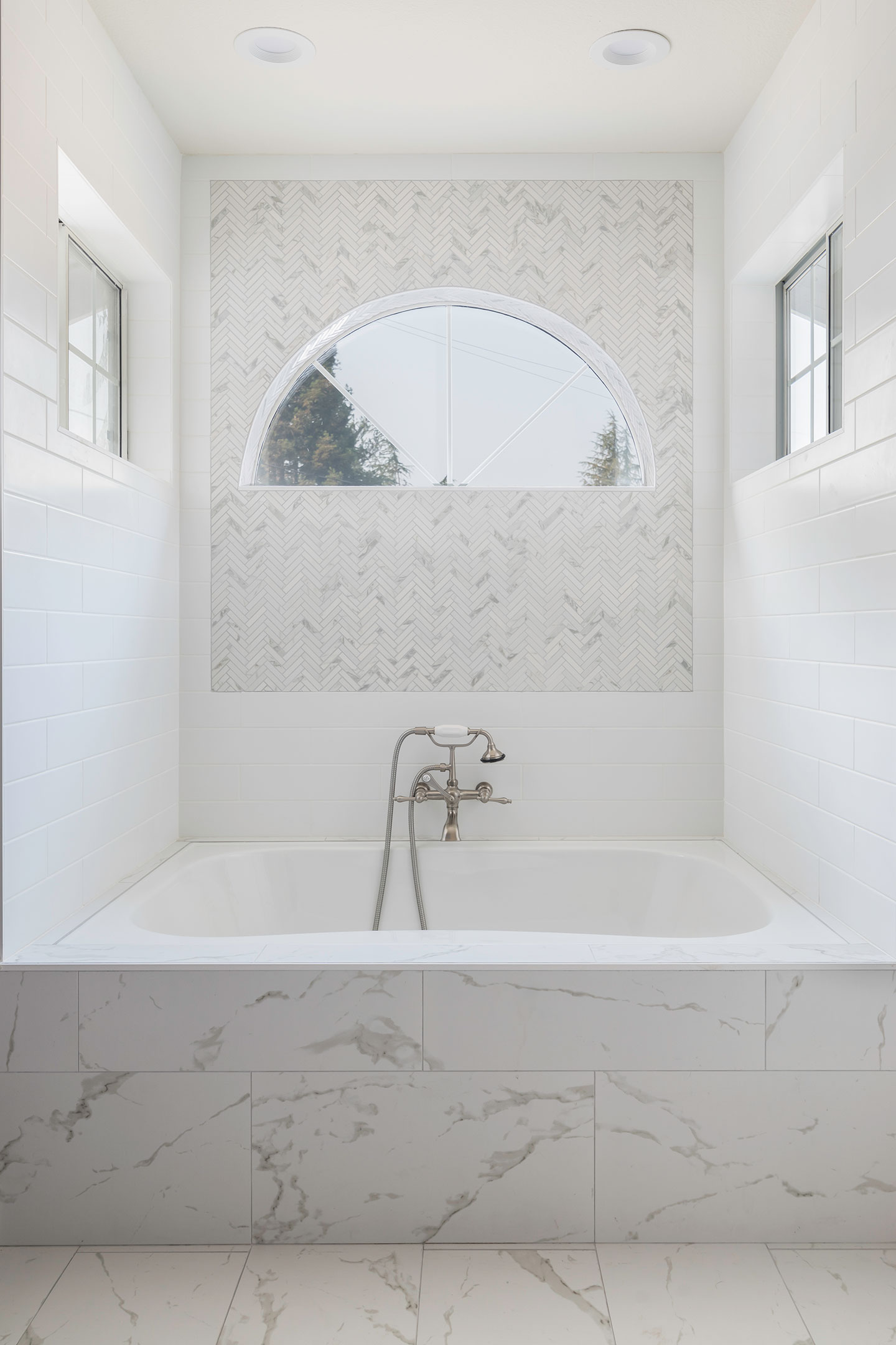 marble drop in bath area with arch window overhead