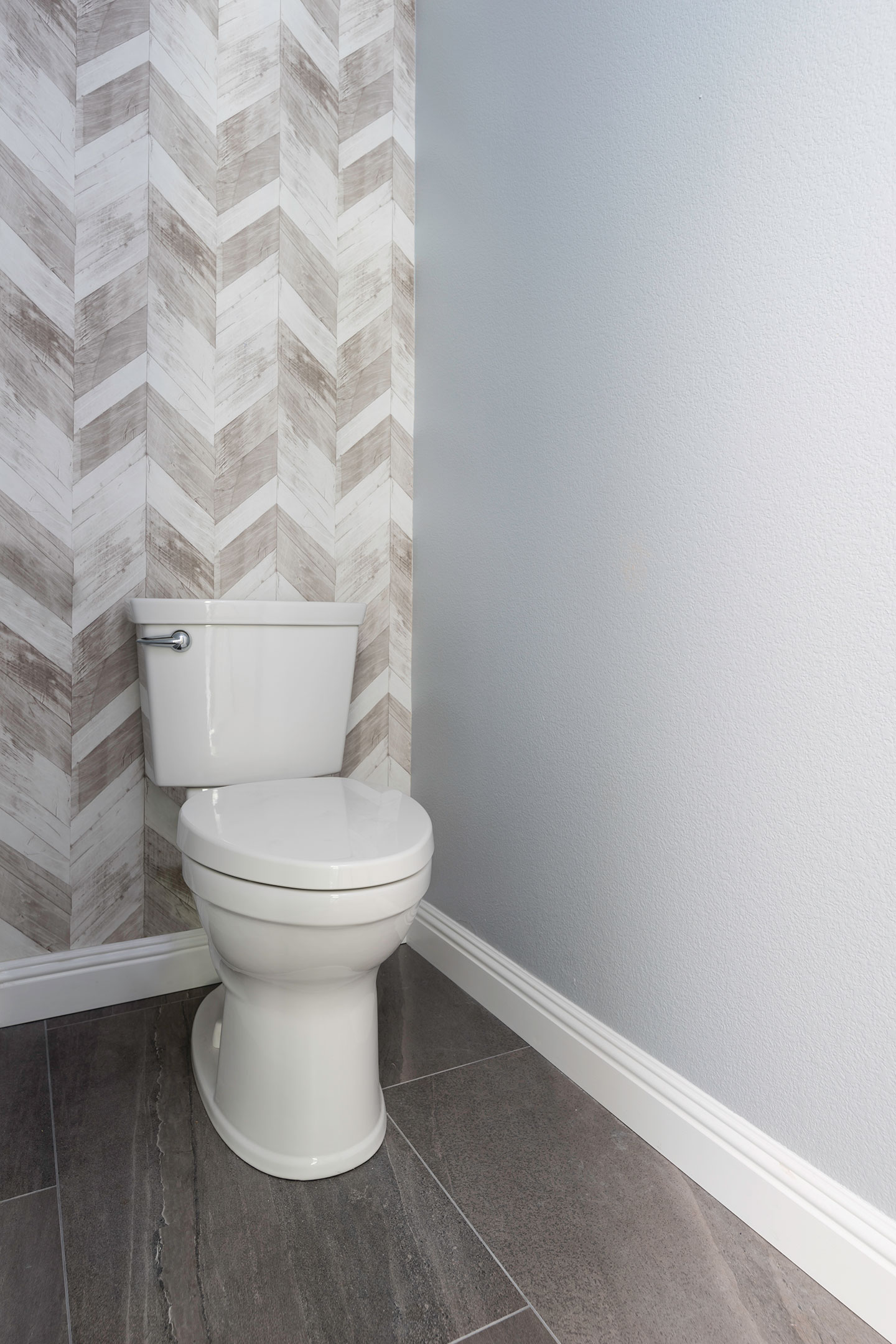 toilet area with a herringbone back wall
