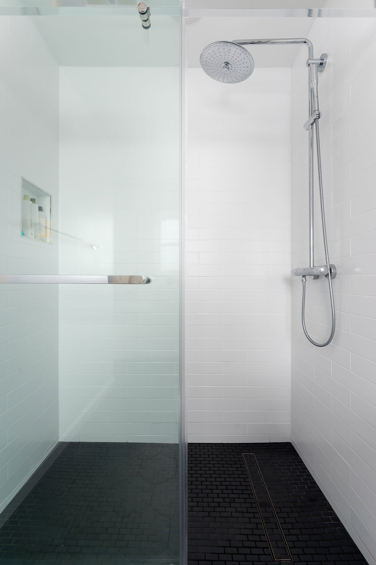 shower area with white tile walls and black floor tiles