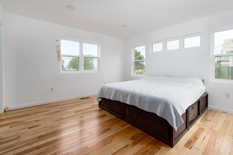 master bedroom with hardwood floors and generous windows
