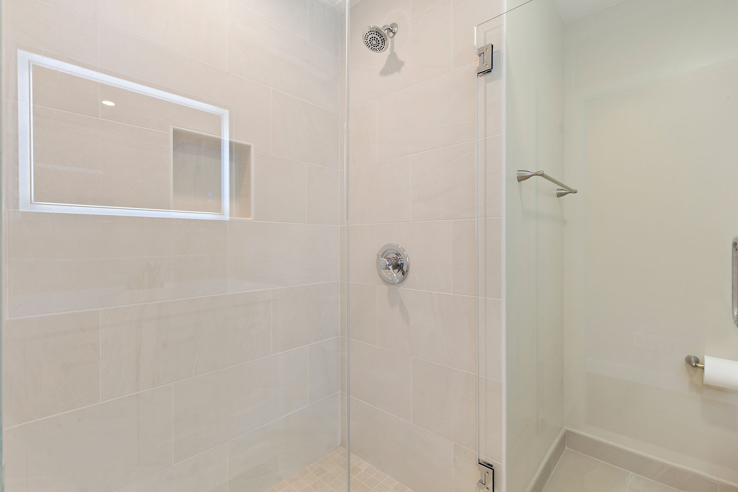 tiled shower area with glass enclosure