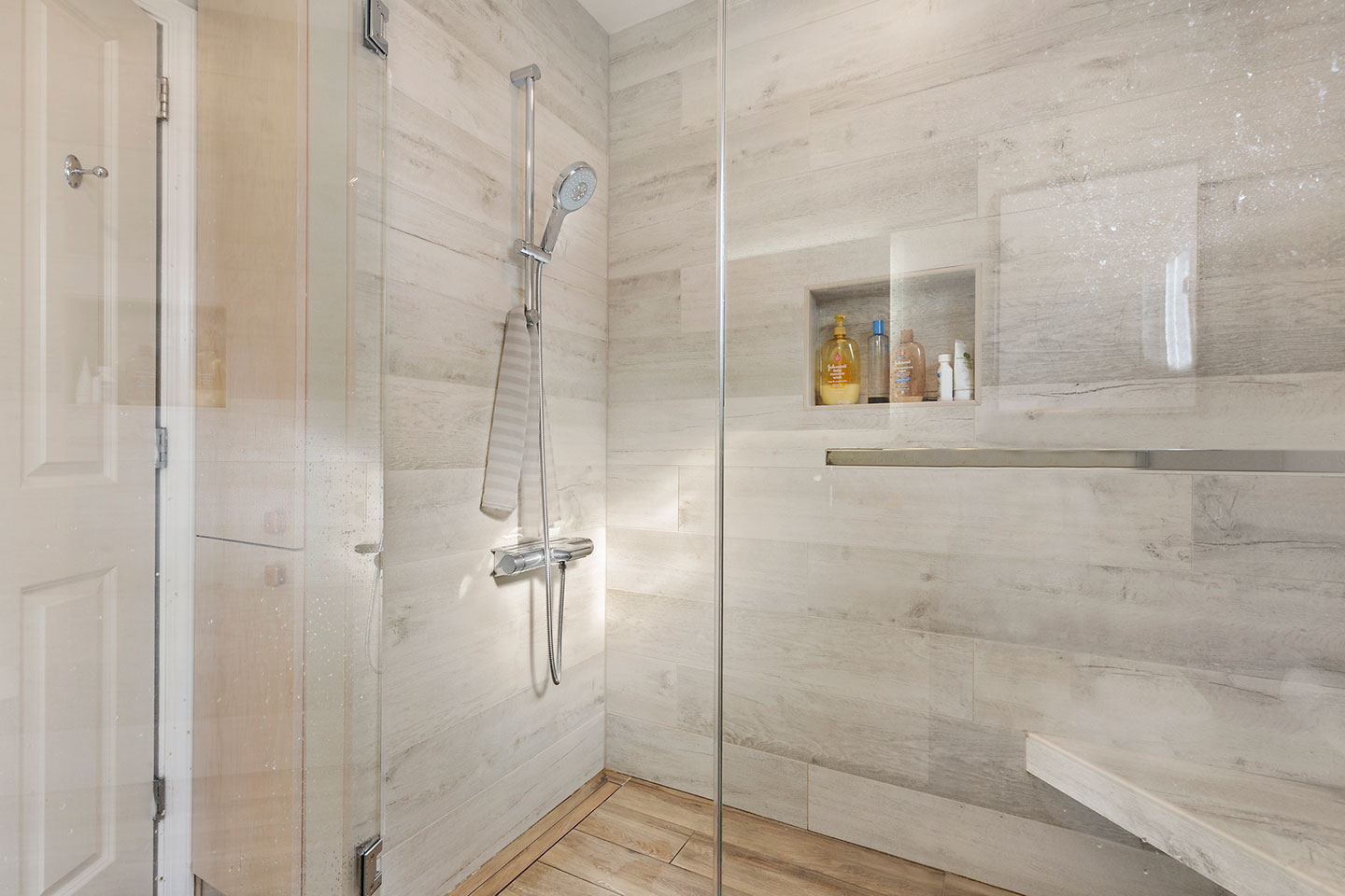 glass enclosed shower area with faux wood tile