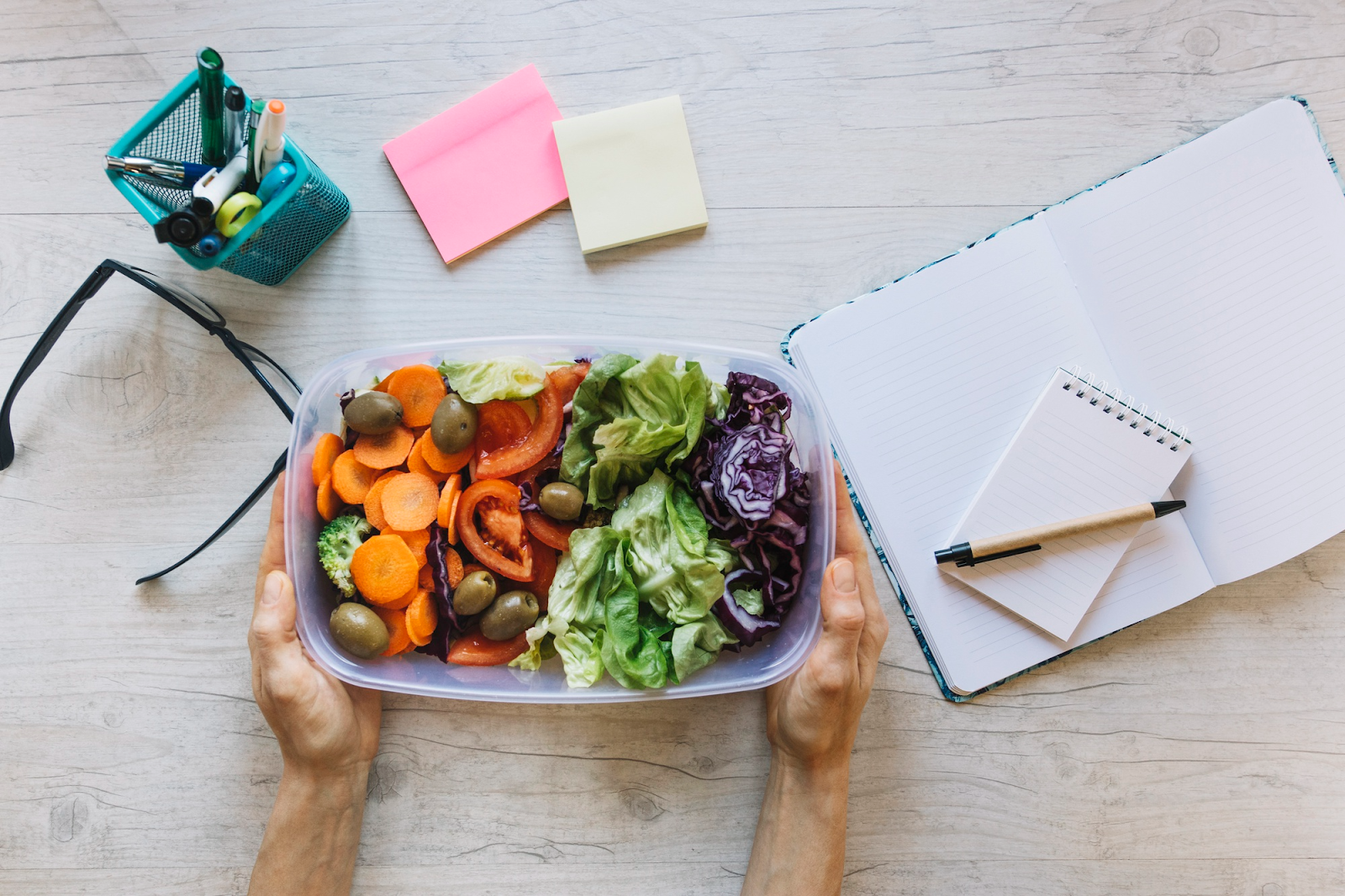 crop photo of hands holding a bowl of salad on office table