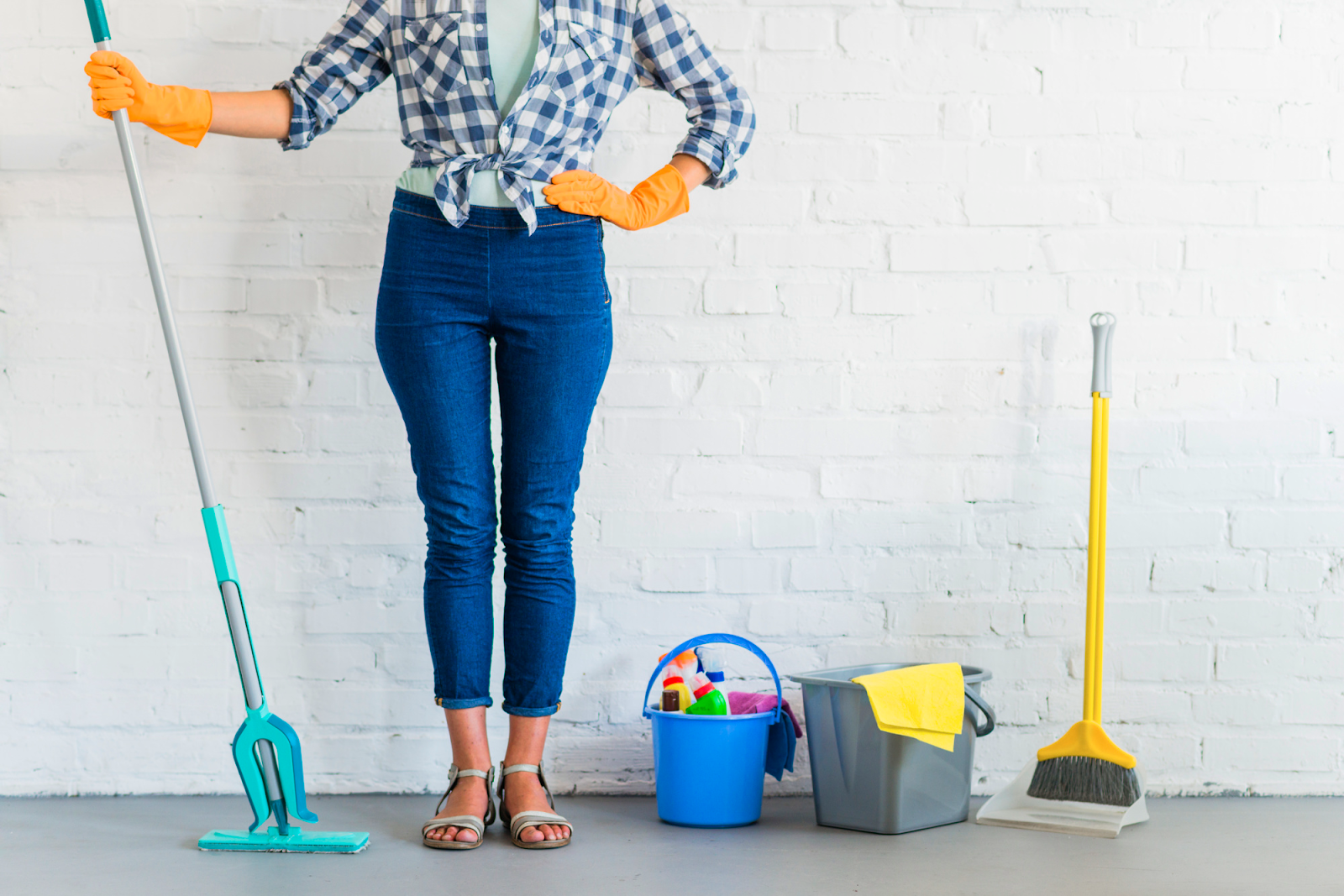 lady standing in front of brick wall holding cleaning equipment