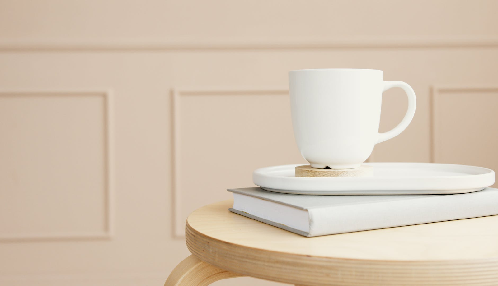 white cup on top of book on wooden table