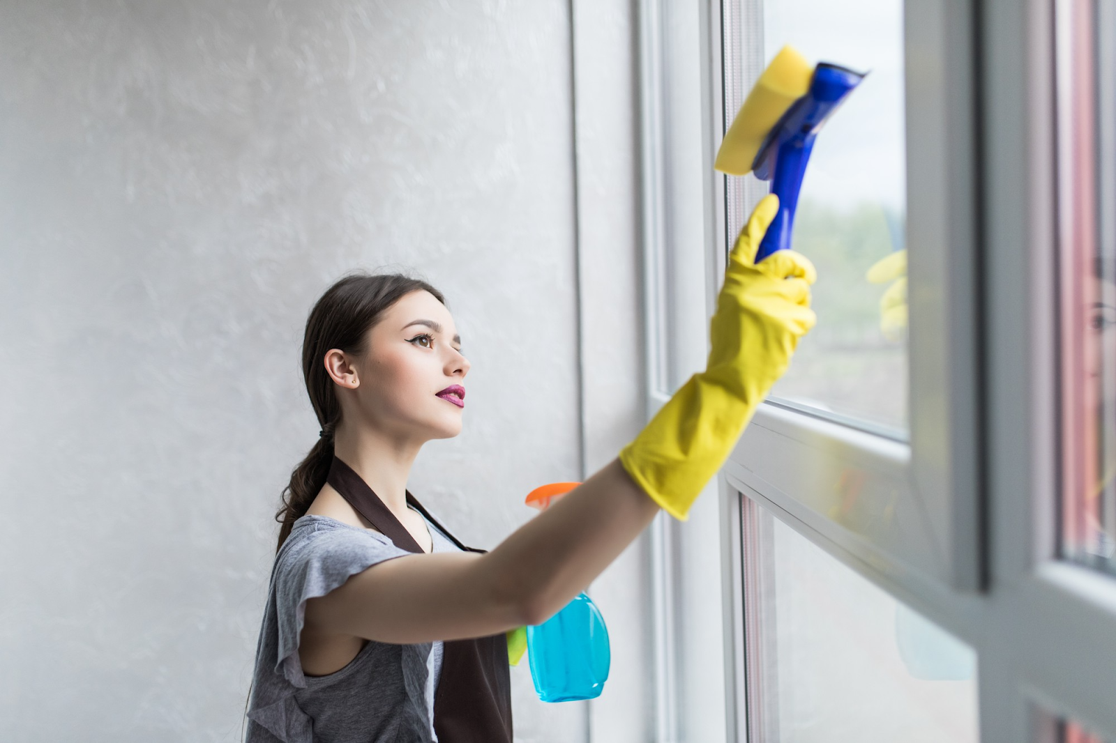 woman in gloves wiping dust from windows