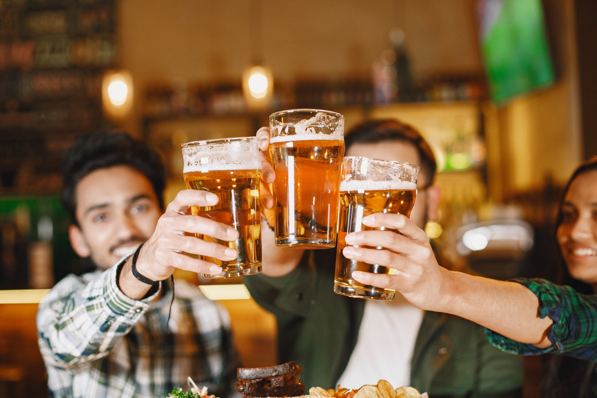 three friends holding up beers