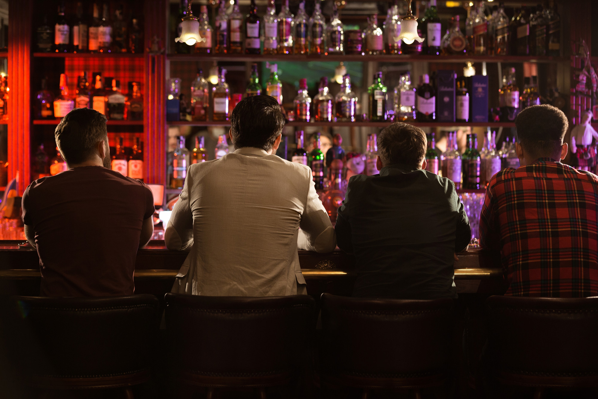 Four men sitting along the bar counter
