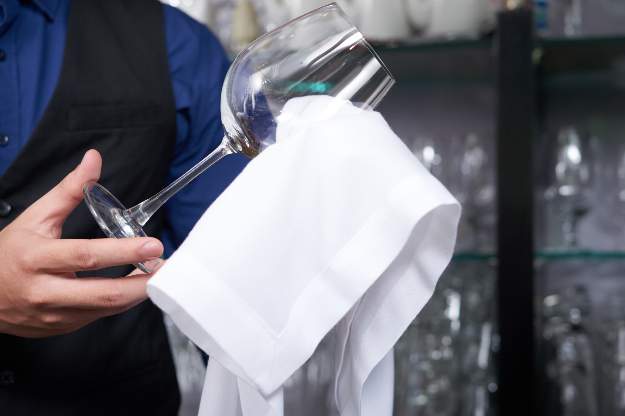 server wiping wine glass with cloth