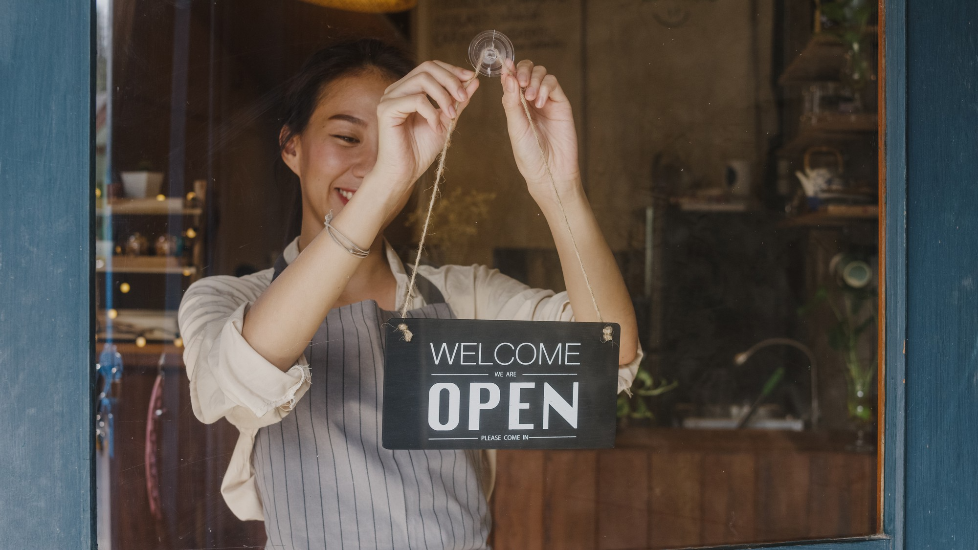 young woman placing open sign in restaurant