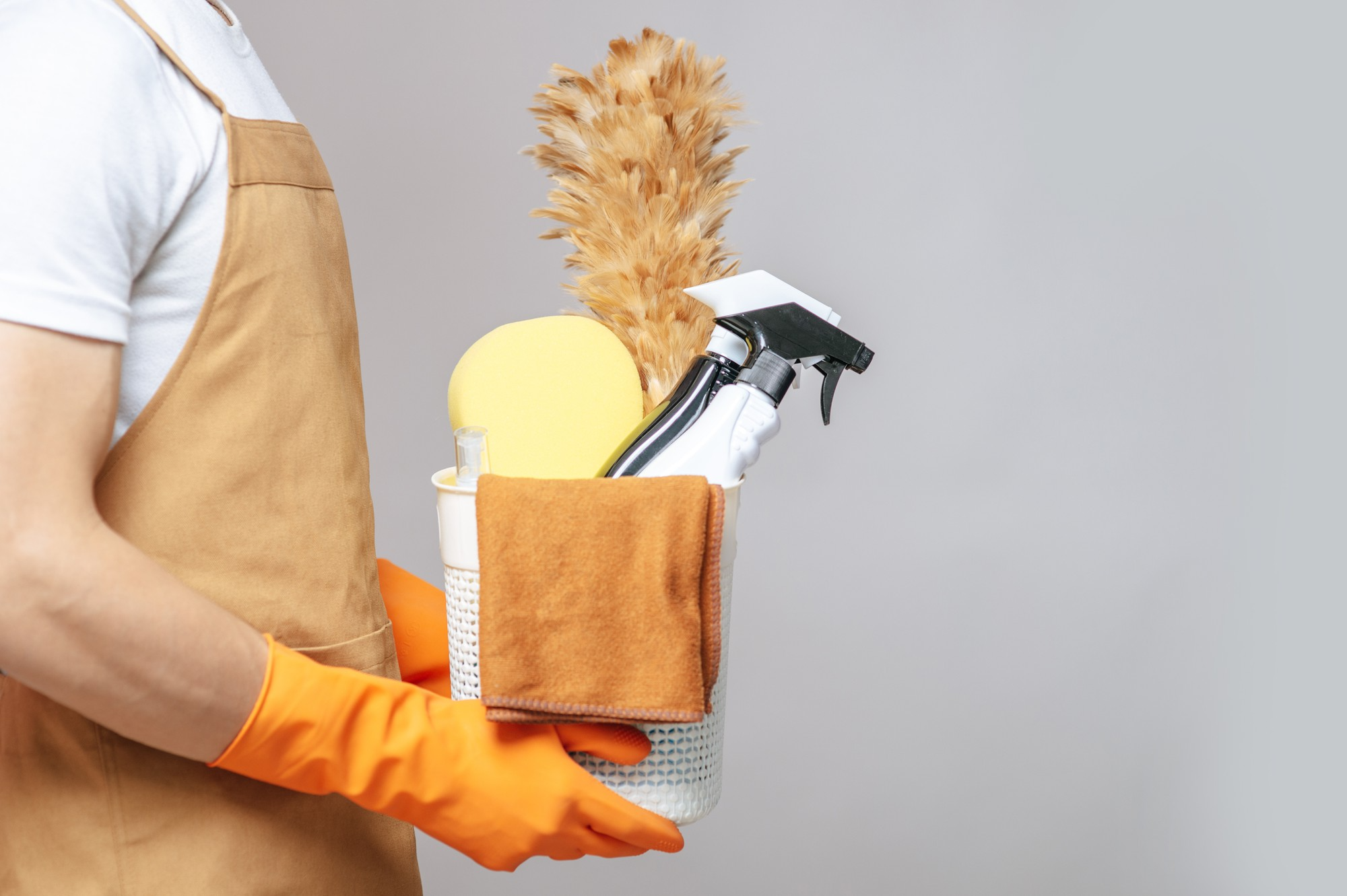 man holding bucket with cleaning supplies