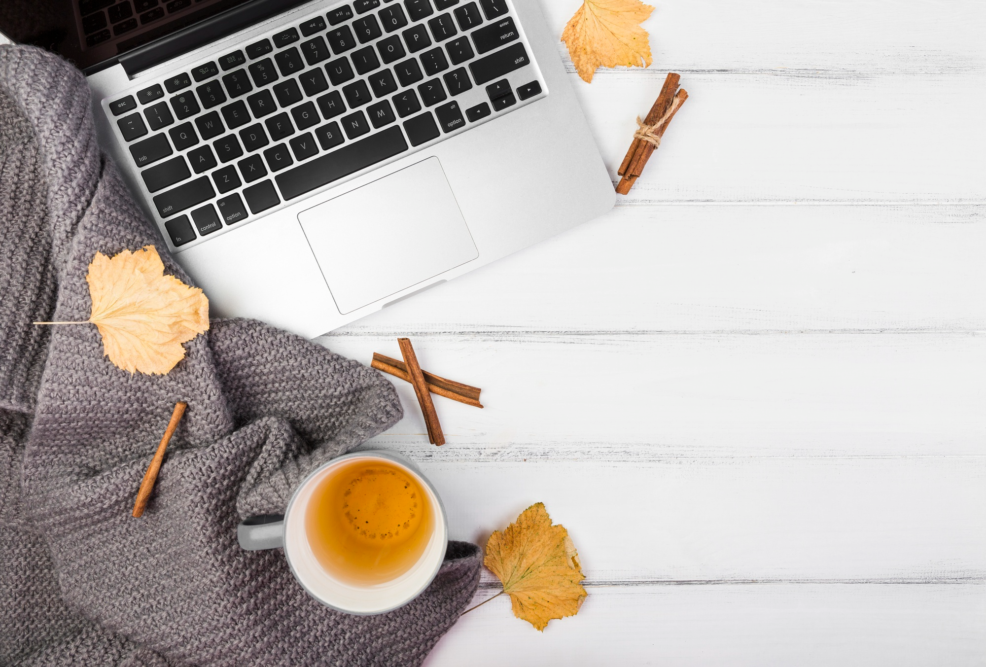 laptop and scarf surrounded by autumn leaves, cinnamon sticks, and tea.