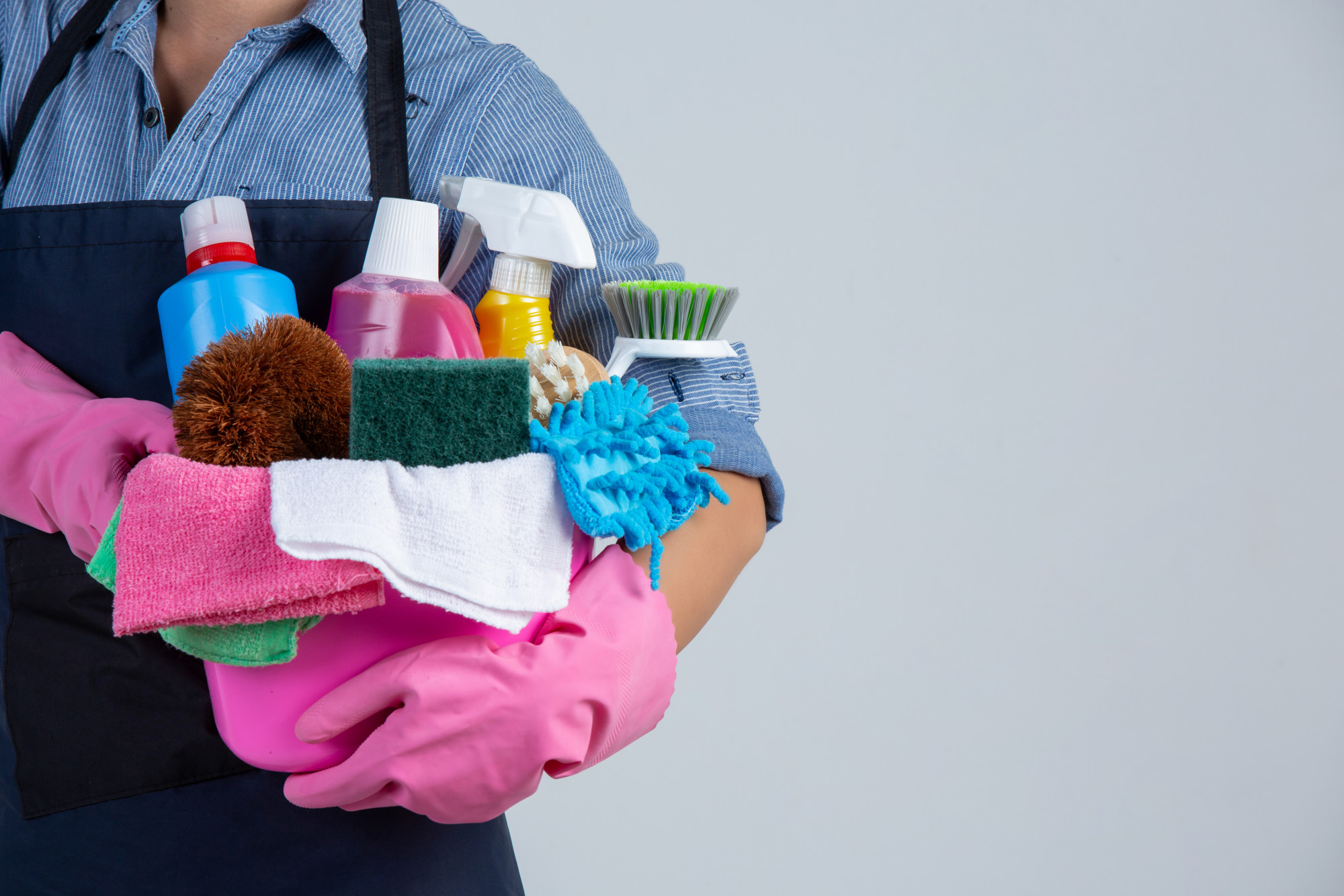 cleaning lady holding cleaning supplies