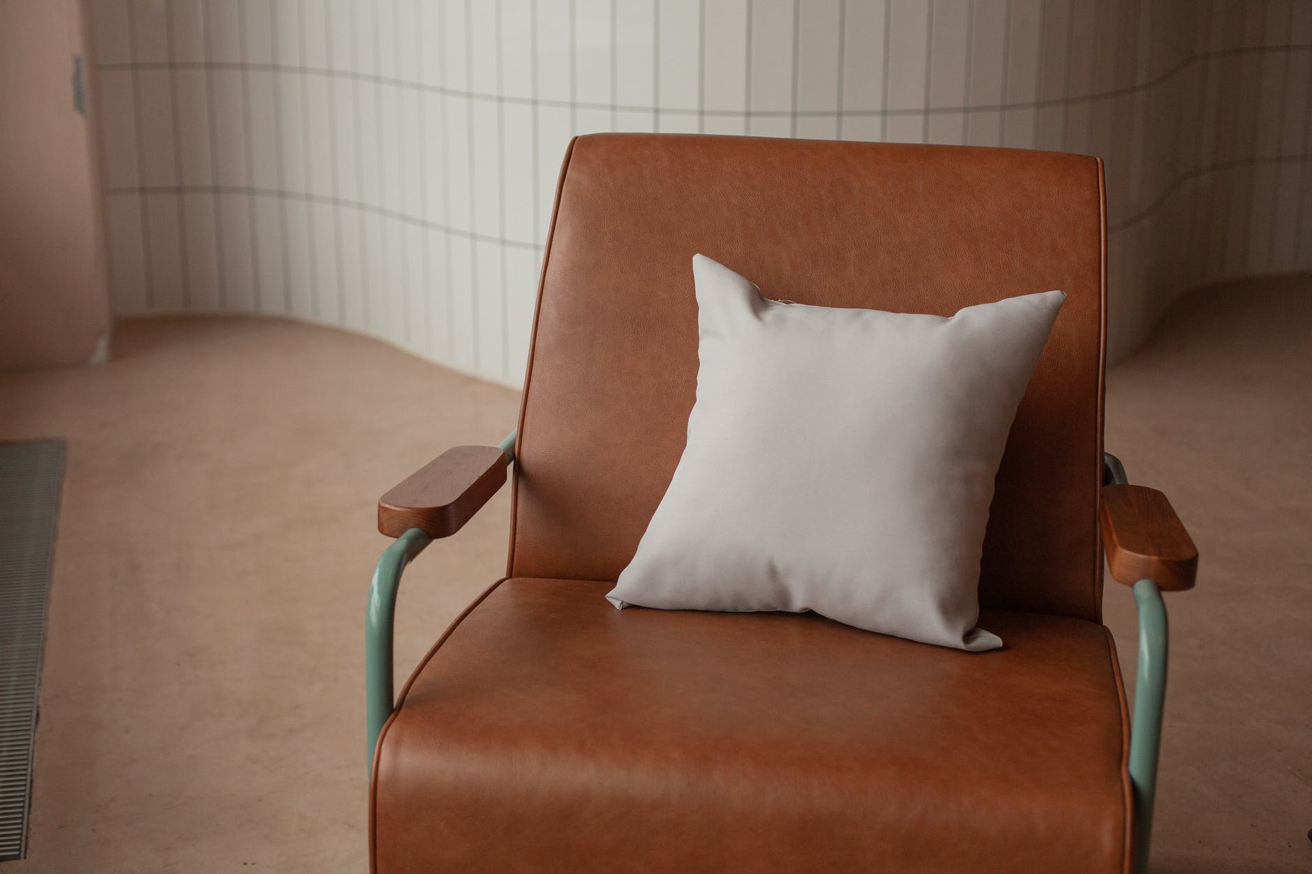 Brown leather chair with pillow.