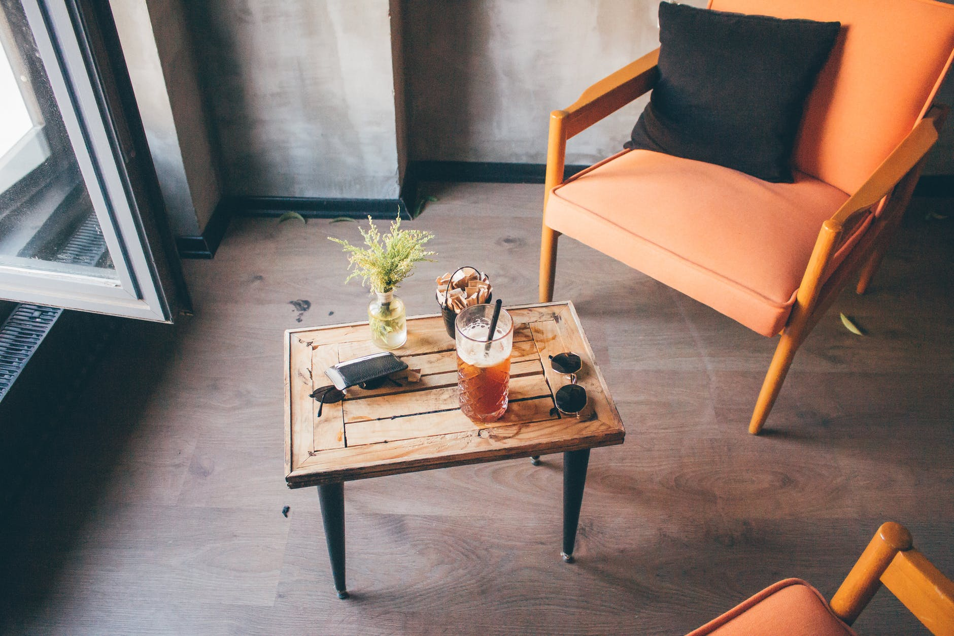 Iced tea on small table and orange leather chairs