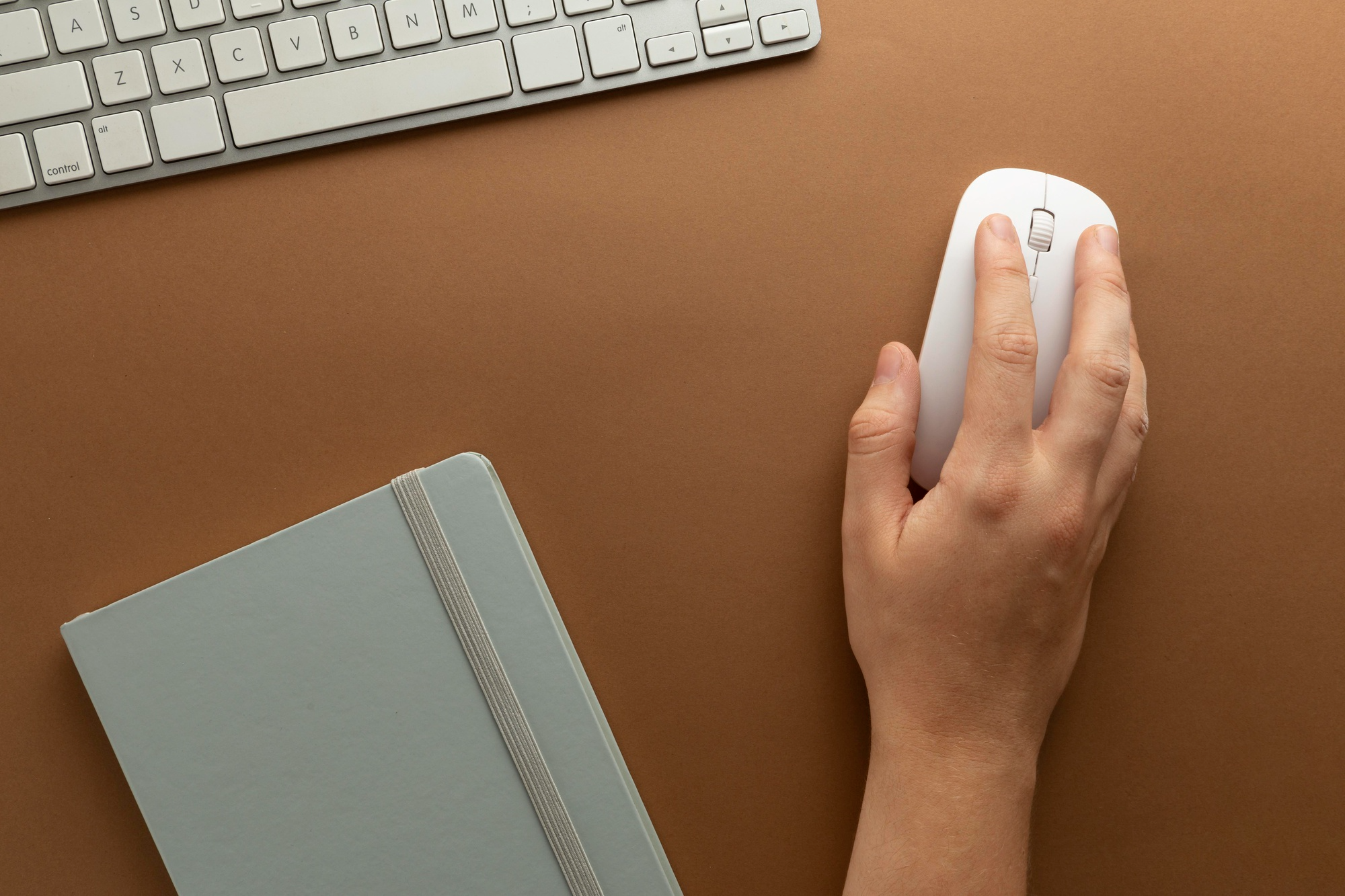 Hand holding wireless mouse on work desk
