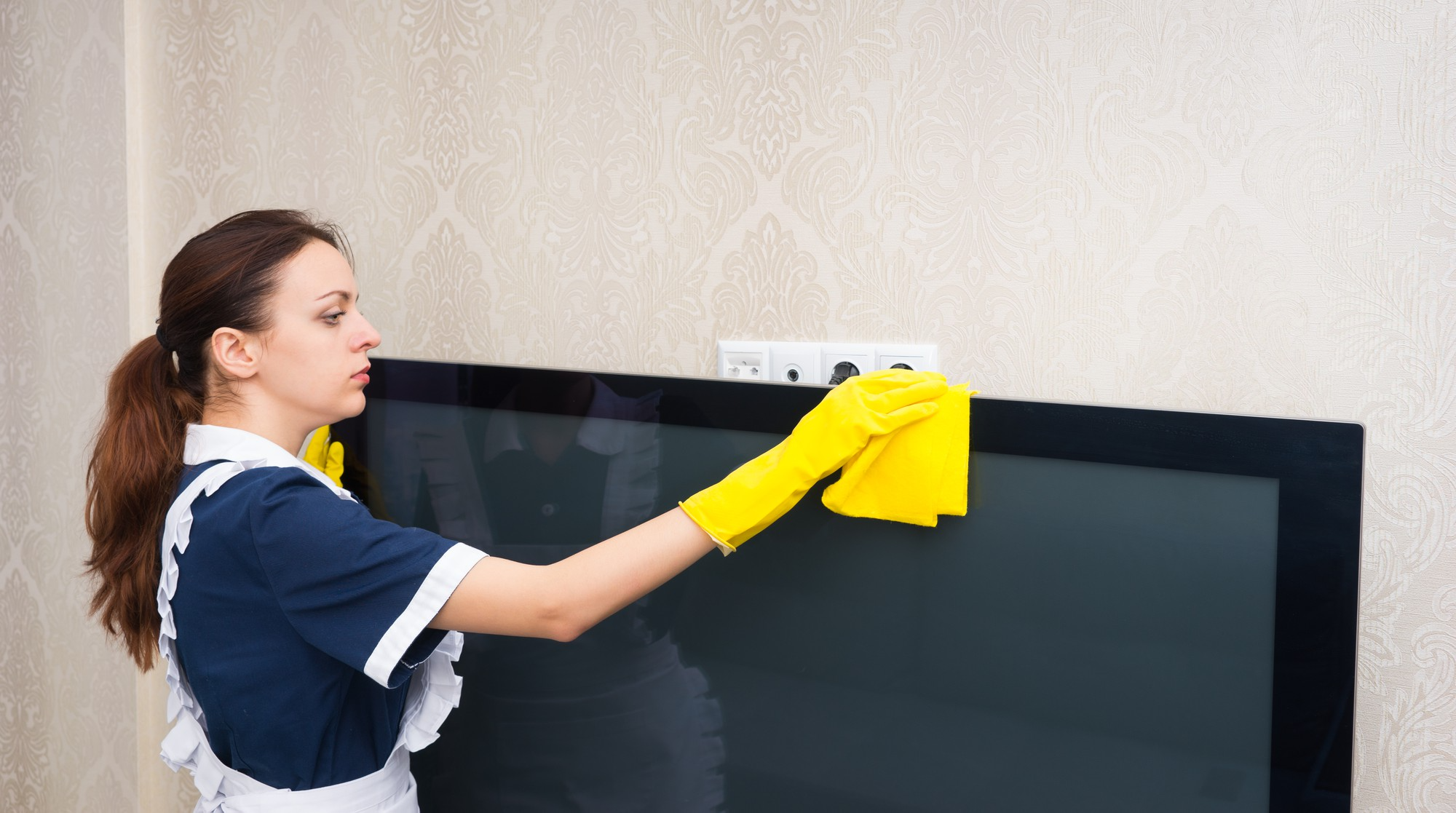 Professional cleaner wiping flat screen monitor