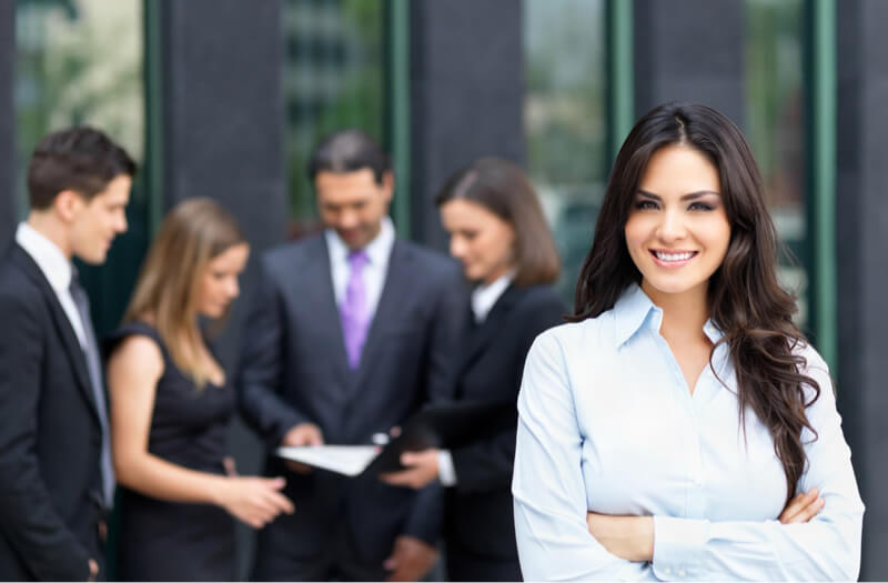confident businesswoman with colleagues in background