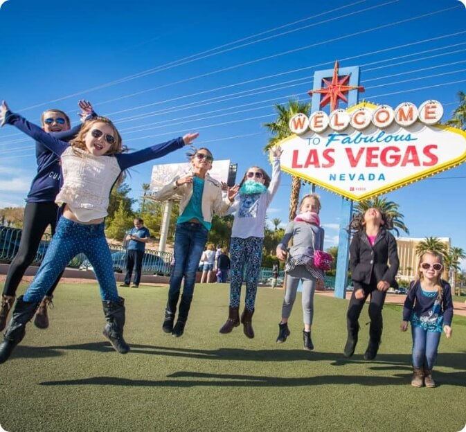 Children happy and jumping next to the Las Vegas Welcome sign
