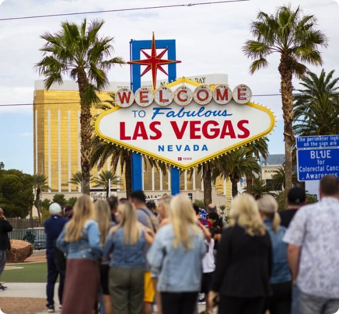 People standing infront infront of Las Vegas welcome sign