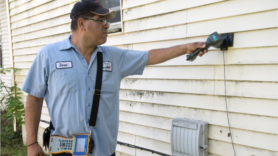 male worker taking a meter reading on the exterior of a residential home