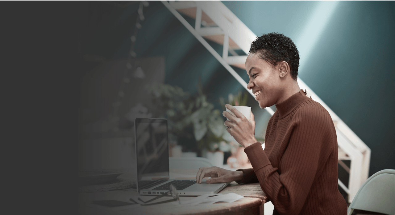 women holding a coffee cup working on her laptop