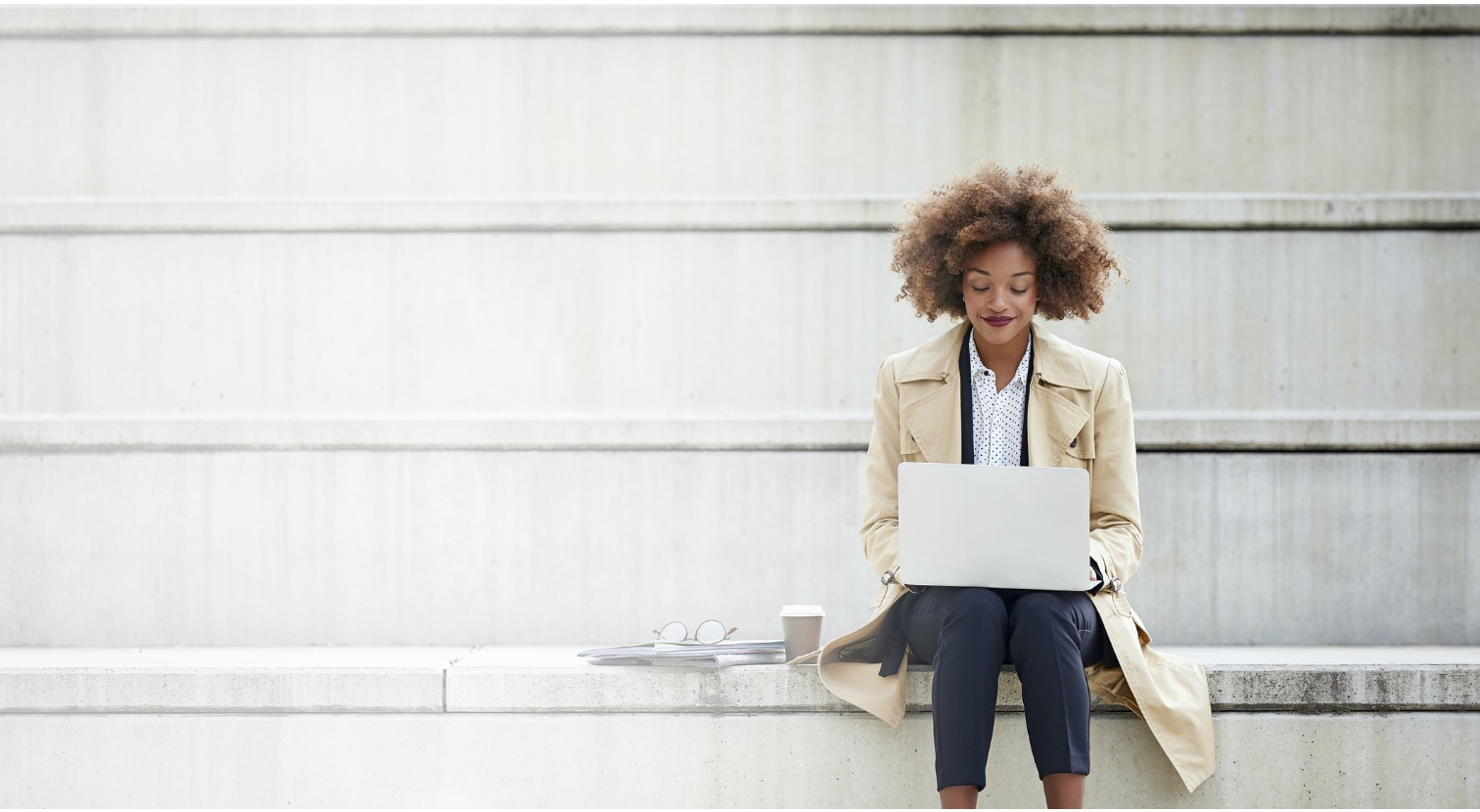 young African American woman sitting on steps using laptop