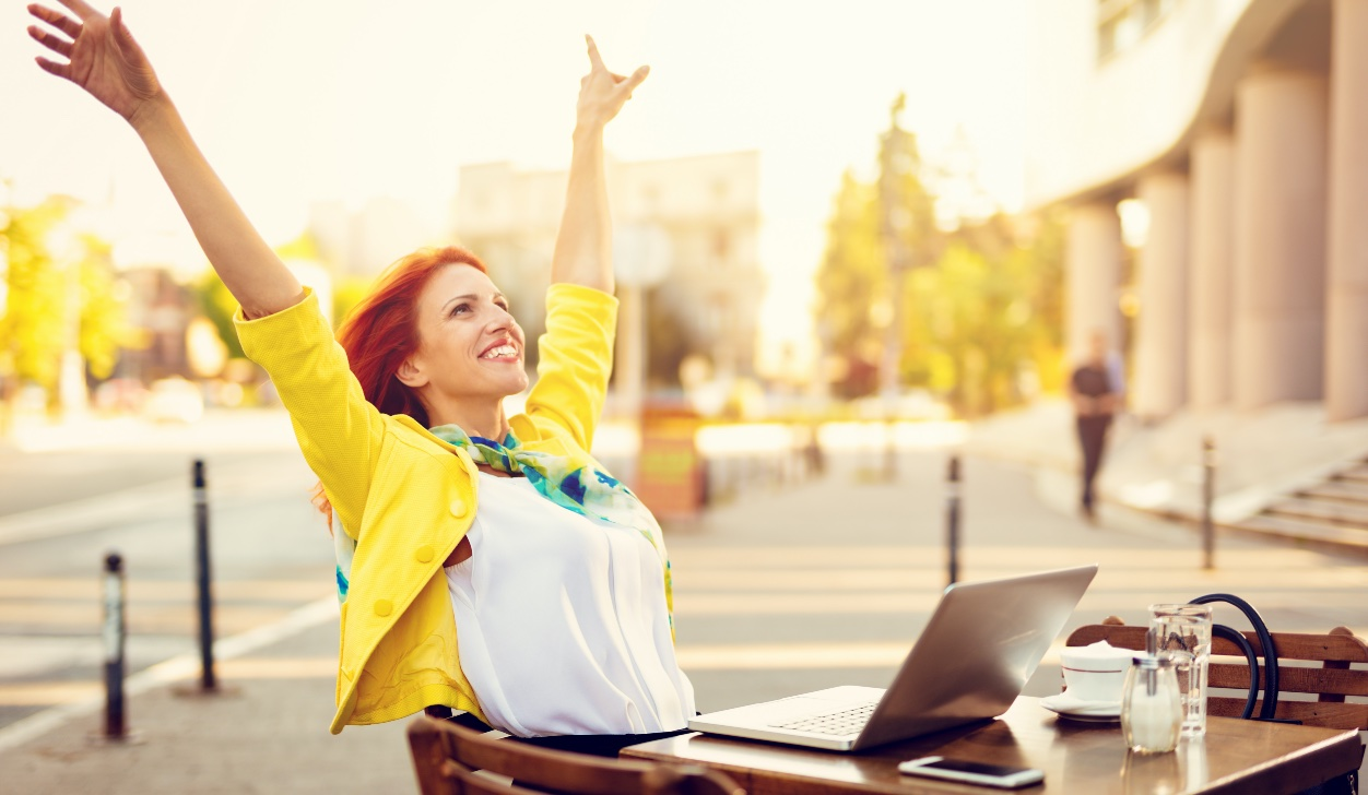 woman in yellow jacket smiling with arms raised looking at computer