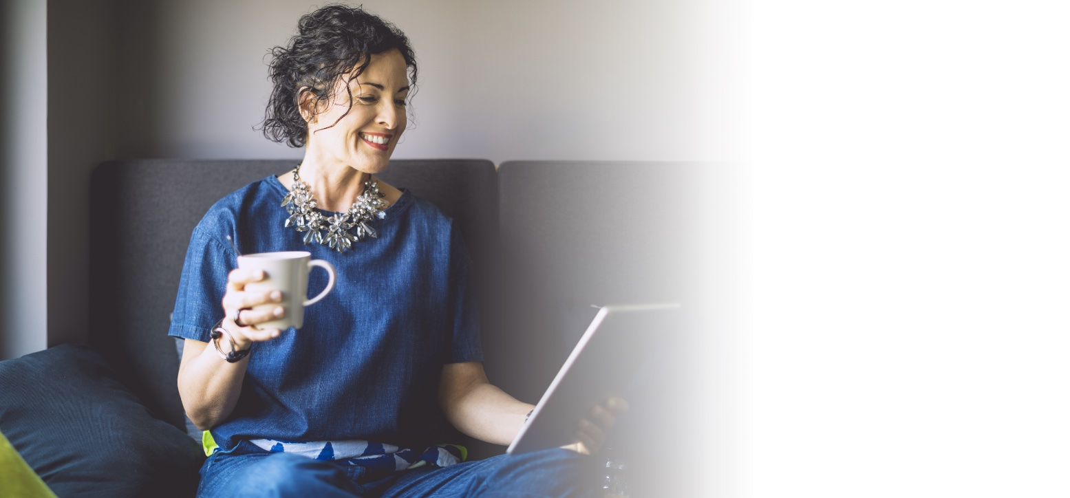 woman in blue dress with coffee smiling looking at tablet