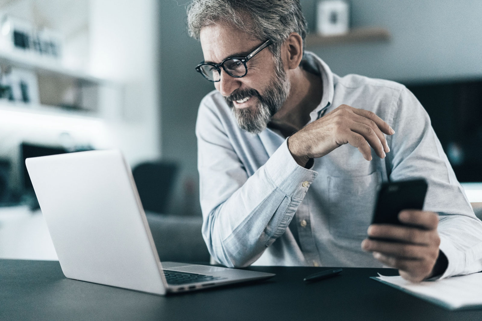man with beard smiling holding smart phone looking at computer