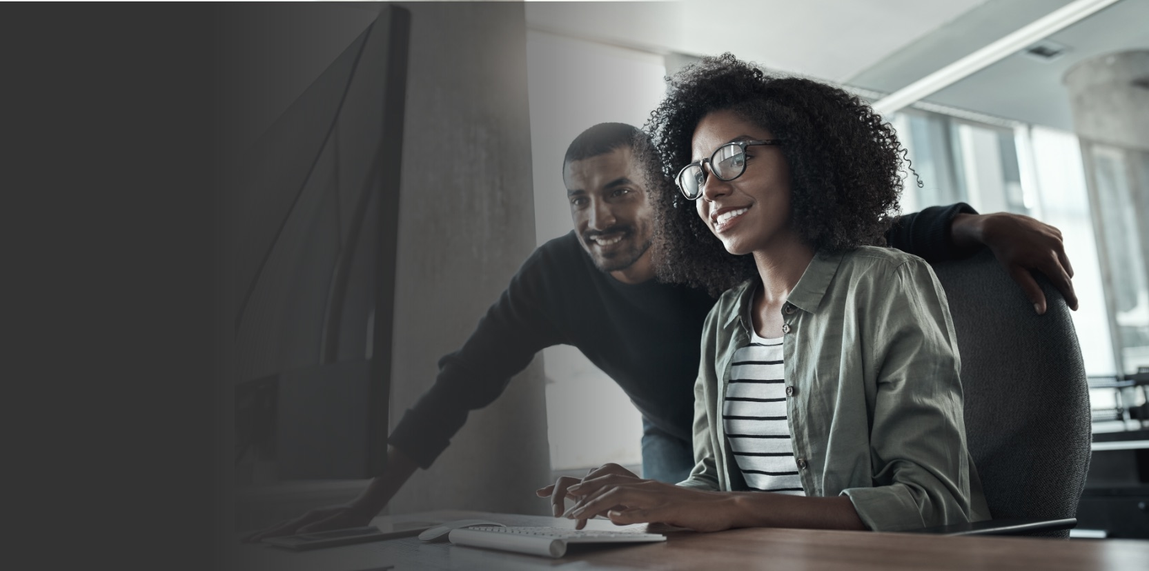 African American man and woman smiling looking at computer
