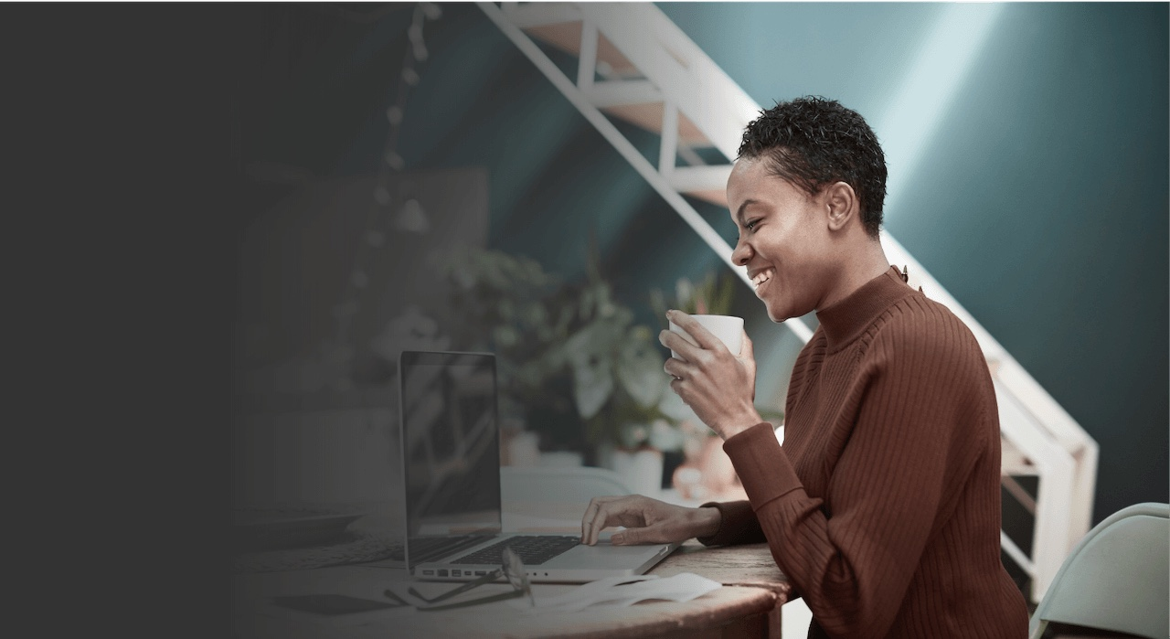 African American woman looking at computer smiling with coffee