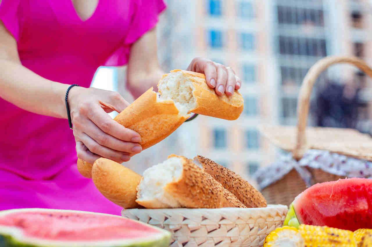 mulher partindo pão e uma mesa com comidas saudáveis