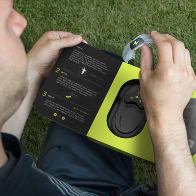 person on sports field taking zone mouthguard out of neon green and black packaging