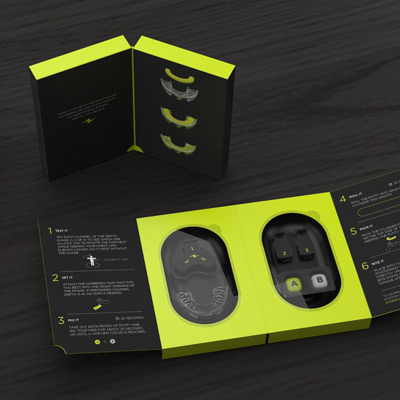 person on a sports field taking zone mouthguard out of black and neon green packaging