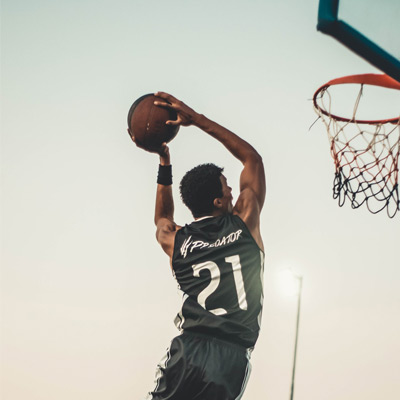 male jumping and dunking a basketball into a hoop outdoors