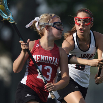 two white females on sports field playing lacrosse