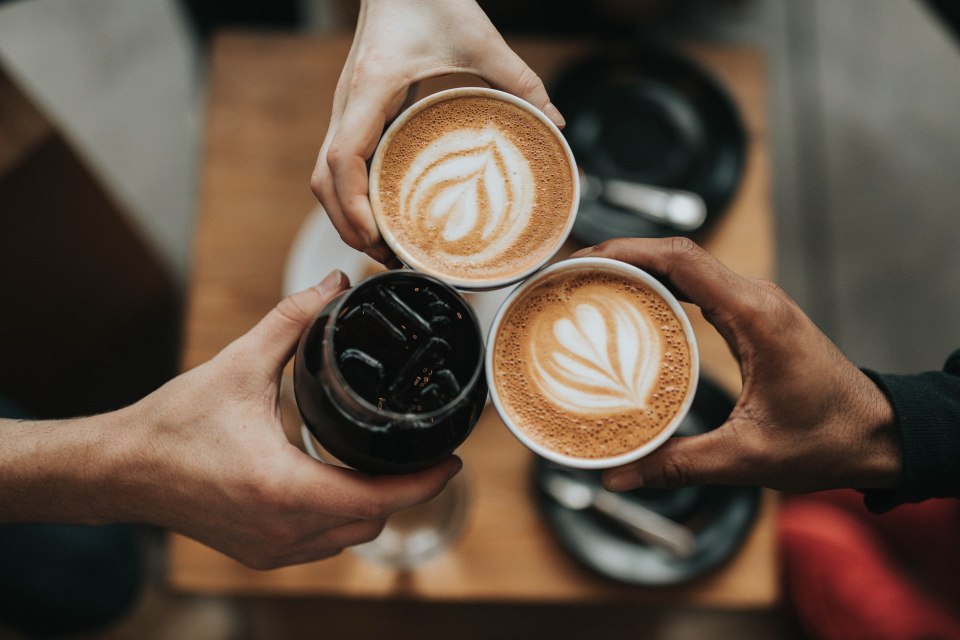 Top-view photo of three hands joining three cups of coffee in the middle of the shot