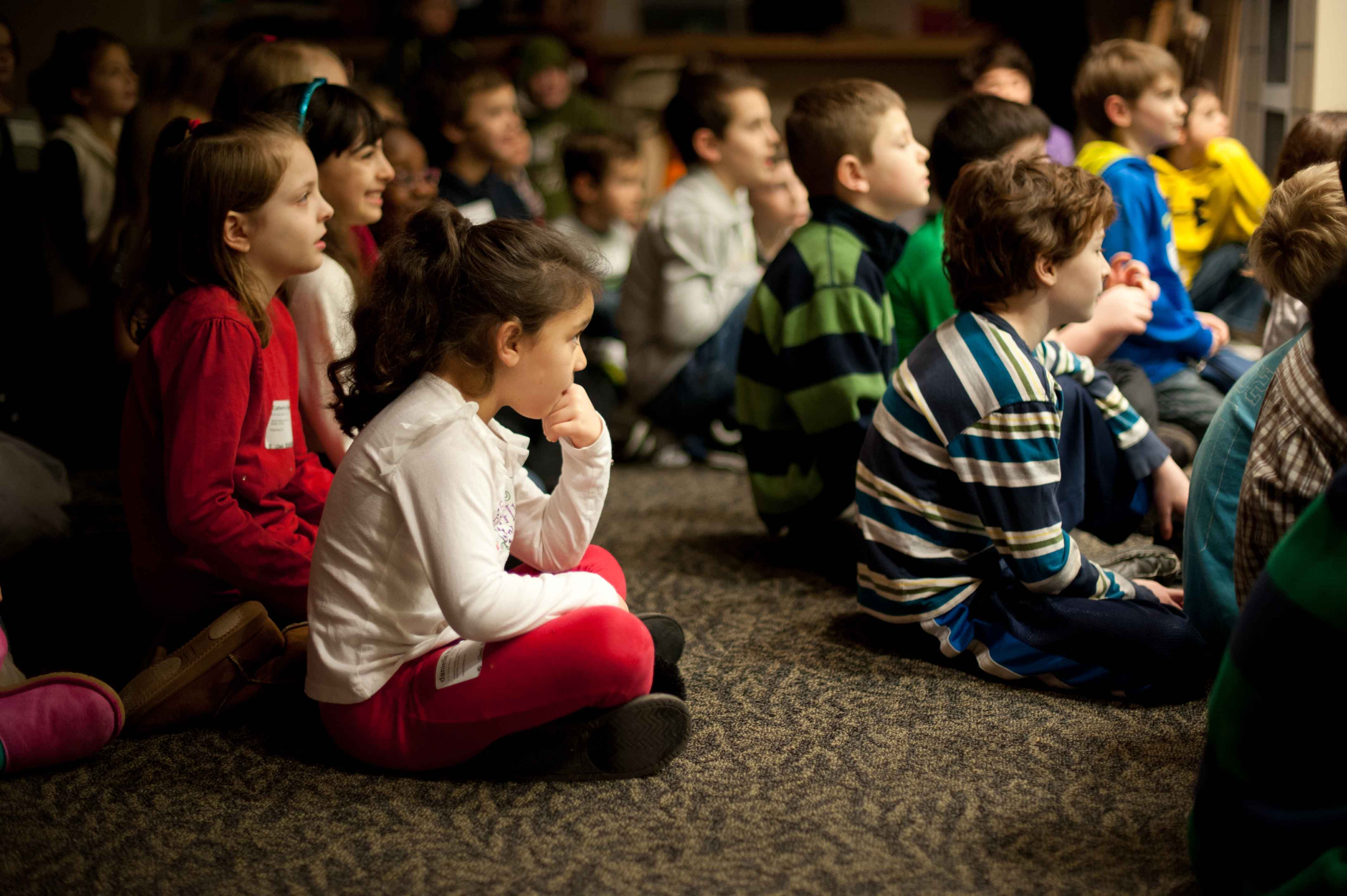 A large group of kids sitting down while learning and listening to someone talk.