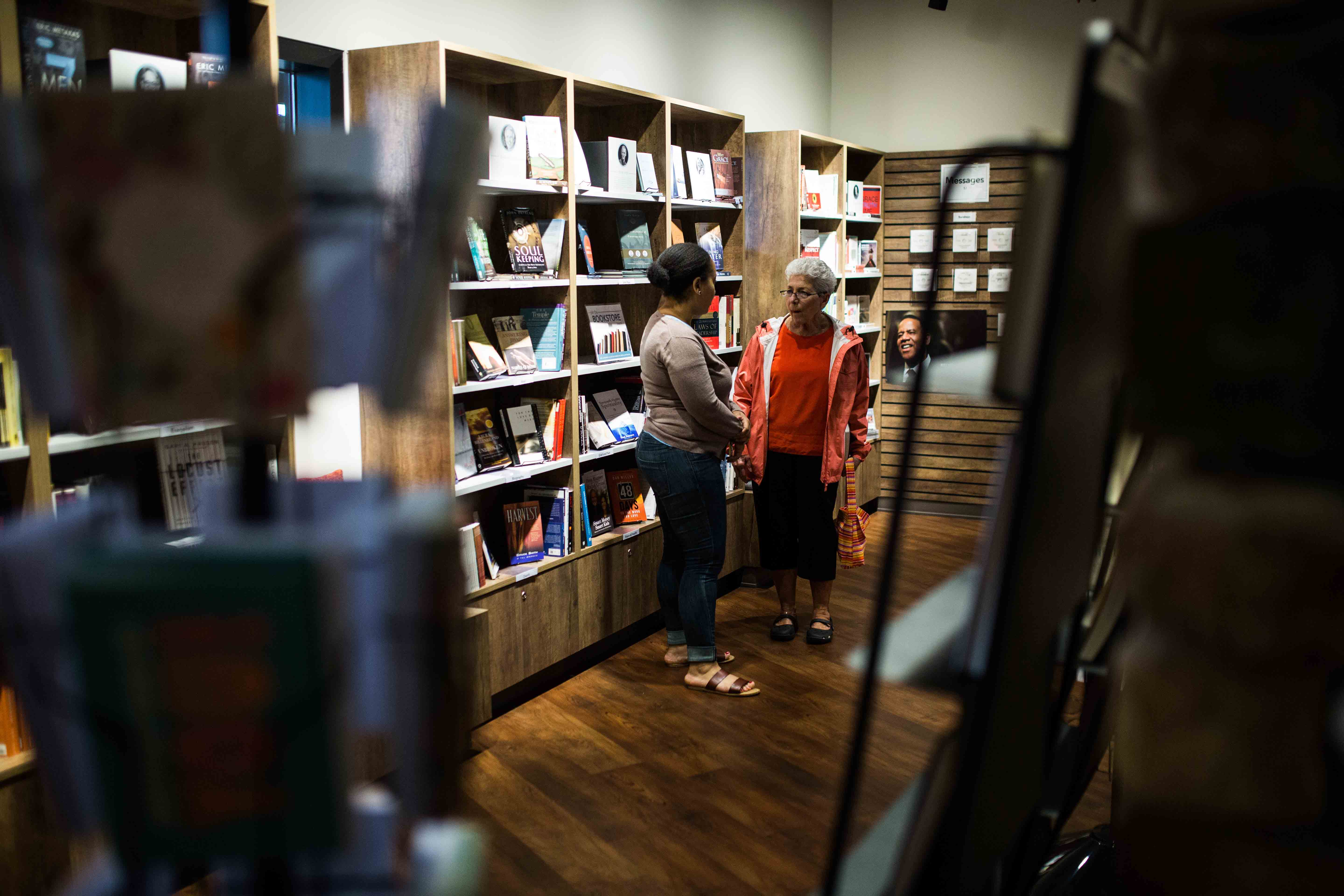 Two older people talking in a moody bookstore.