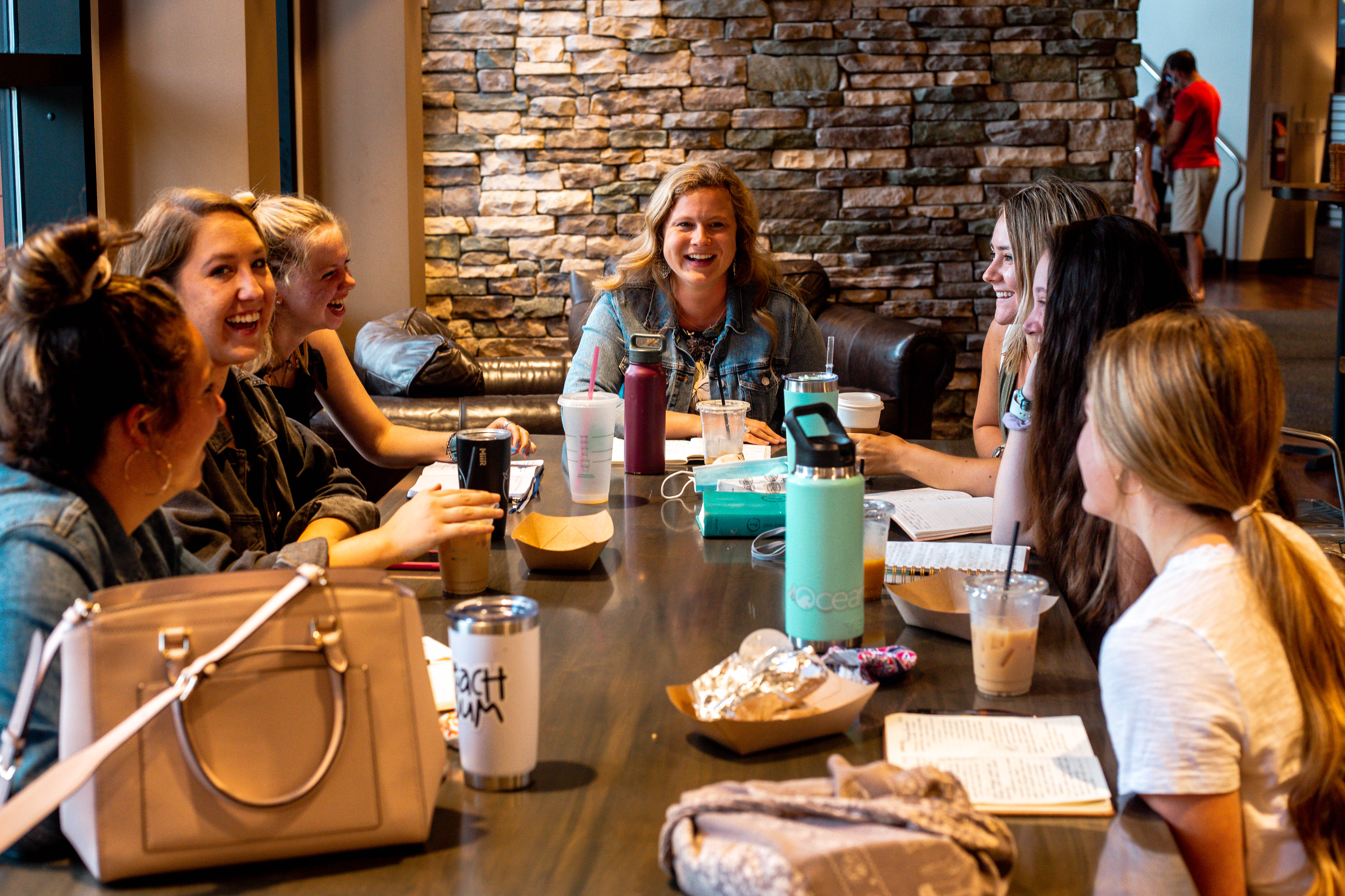 A happy group of women sitting at a table enjoying fellowship.