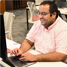 A man at his desk smiling