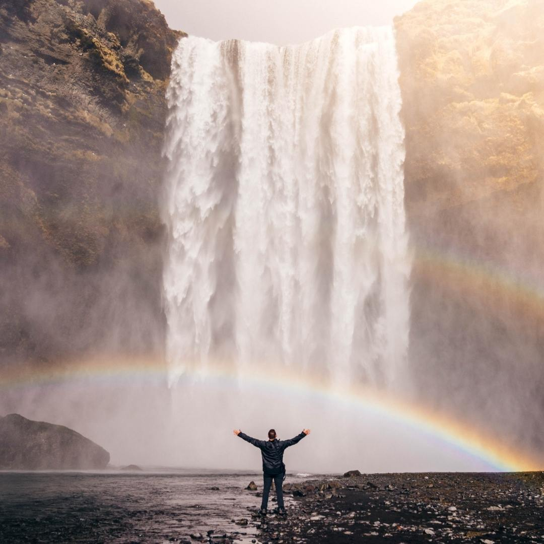 person lifting arms in front of waterfall and rainbow life ego identity let go freedom joy peace tranquility