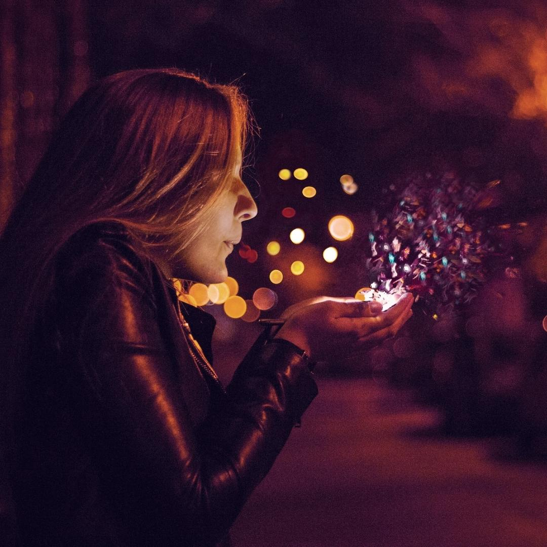 woman blowing glitter or confetti at night | creativity create creative energy positive