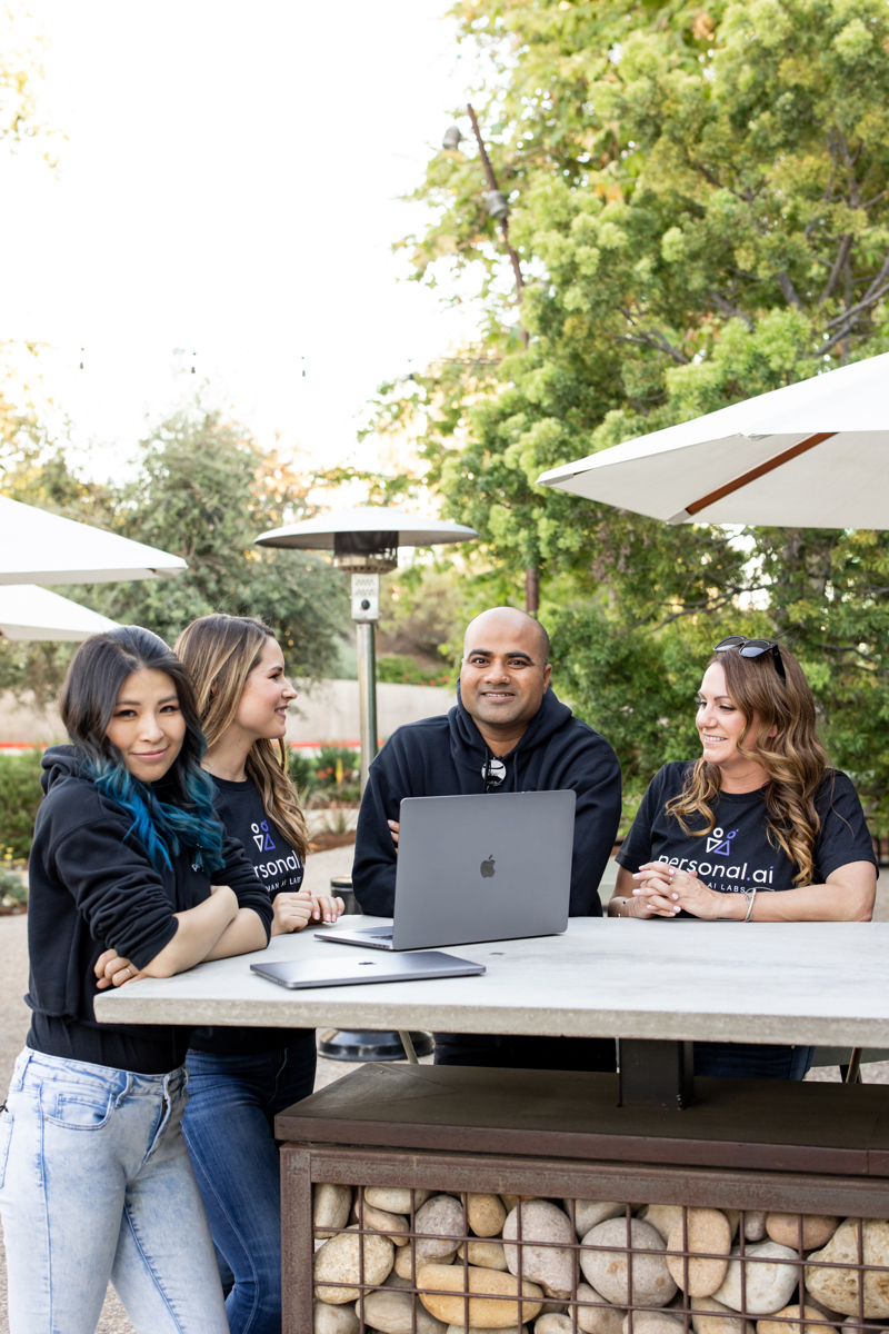 Personal AI team gathered around a laptop outside at a public workspace. They're probably thinking about how to code the best data privacy for their customers!