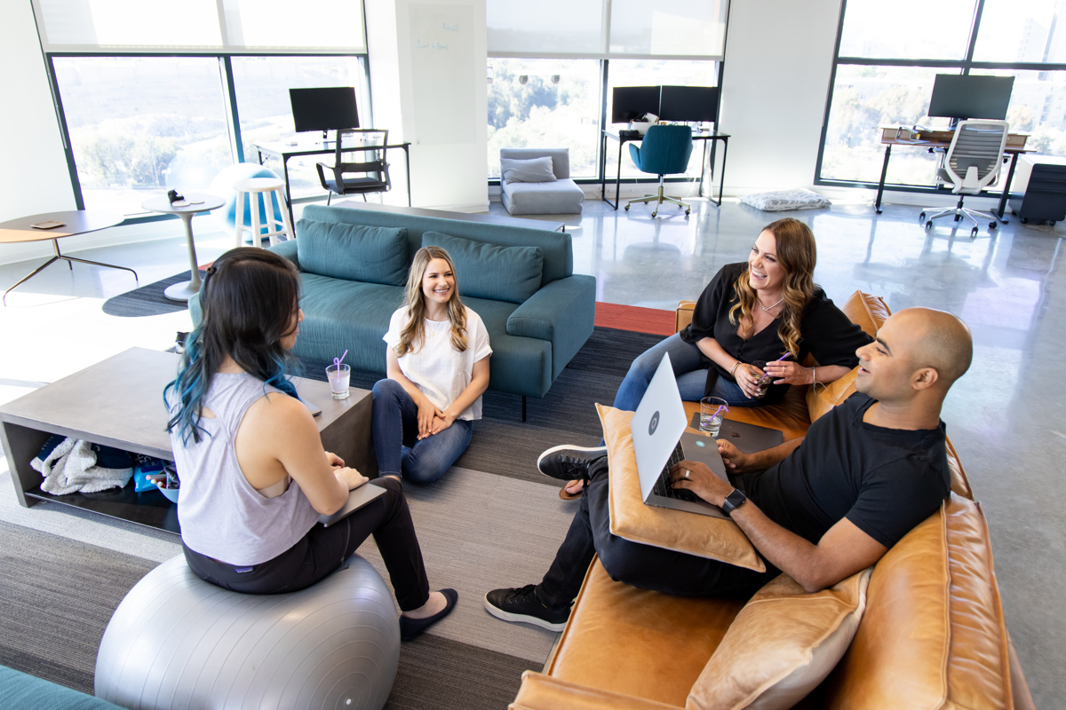 The Personal AI team sits in a circle working in our beautiful San Diego office. They're smiling because they're excited about building ethical AI.