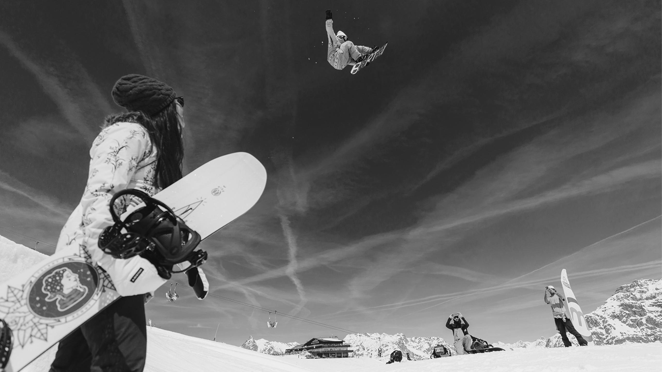 Schwarzweiss Bild von einem Snowboarder im Stunt