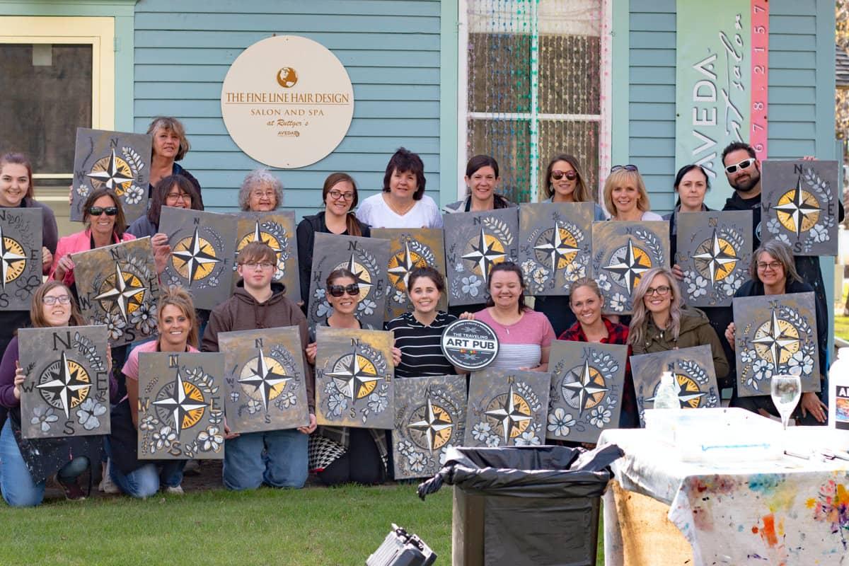 Team building group outside holding artwork